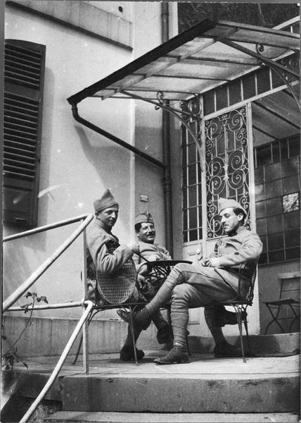 Portrait collectif : trois militaires assis à une petite table, devant l'entrée d'une maison
