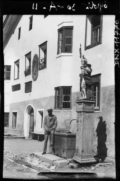 Façade, fontaine ornée d'une statue au premier plan