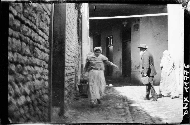 Passants dans une rue : femme portant un seau