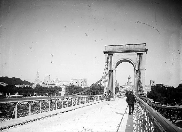 Pont suspendu: piétons et charrettes au premier plan, palais et horloge en arrière-plan
