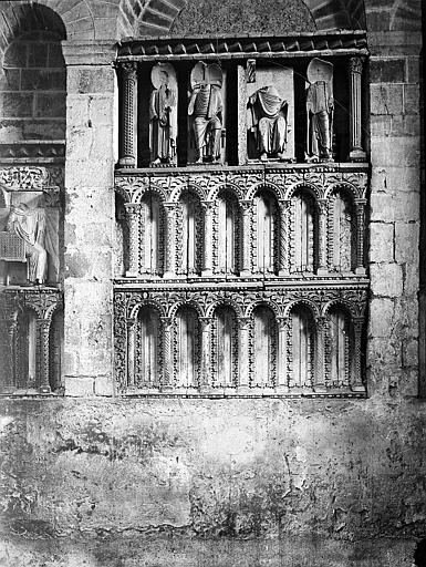 Bas-relief: arcades en bon état et statues détériorées