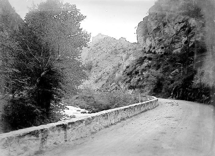 Route longeant une rivière et château en arrière-plan