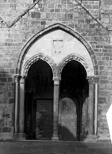 Petit porche à deux arcades séparées par une colonnette centrale semée de coeurs