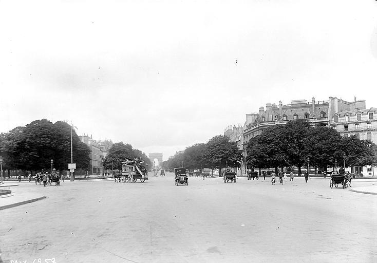 Vue prise du sud-est: arc de triomphe au loin, voitures à cheval au premier plan, dont un transport collectif