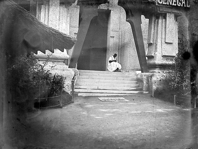 Personnage en costume traditionnel assis sous le porche