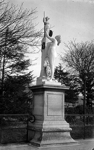 Statue: femme tendant les mains vers une figurine