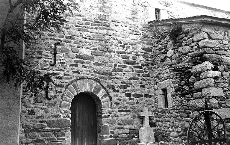 Façade latérale avec la porte de la sacristie et une tombe