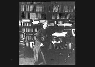 Monseigneur Baudrillart, assis dans sa bibliothèque
