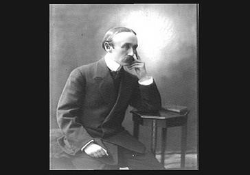 Eugène Berteaux (conservateur des monuments de Paris) accoudé à une table