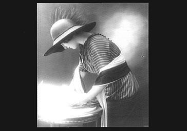 Colette Darly, portant une écharpe et un chapeau