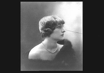 Colette Darly portant une fourrure et un collier, vue de profil