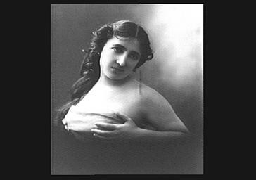 Mlle Dorza, les mains sur la poitrine