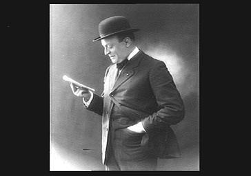 Armand Ménard dit Dranem, chanteur de café-concert, debout et lisant