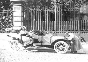 Mistinguett près de sa voiture et son chauffeur devant un parc