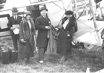 Groupe d'hommes et de femmes devant un avion