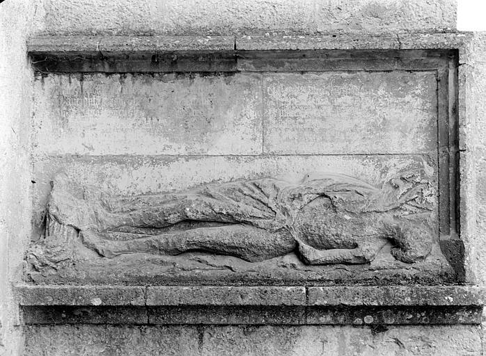 Bas-relief sculpté dans le contrefort, à droite du portail de la façade nord : Gisant