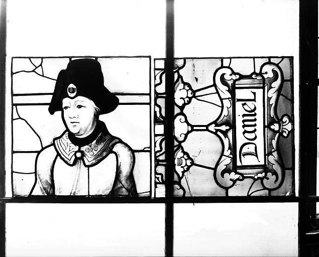 Deuxième galerie, portail sud, lancette de Daniel, titulus et tête