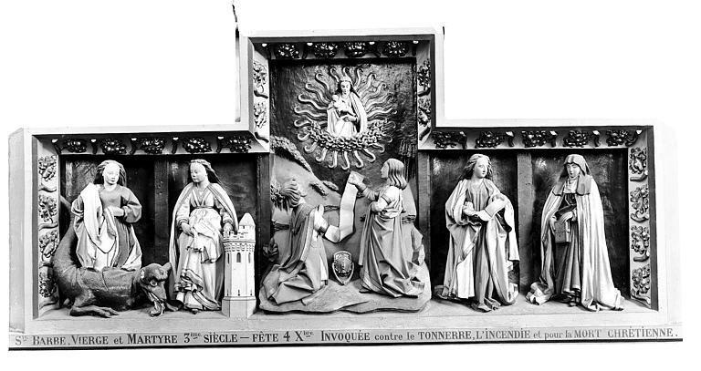 Chapelle du Trépané, retable. Haut-relief du retable de la chapelle du Trépané : La Vierge, sainte Marthe, sainte Barbe, sainte Marguerite, sainte Thérèse et deux donateurs