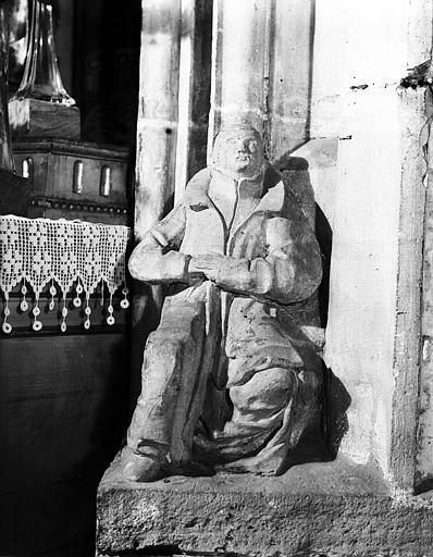 Homme assis sculpté au pied d'un pilier du carré du transept