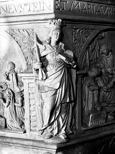 Détail du baptistère : statue d'une femme avec cierge et livre