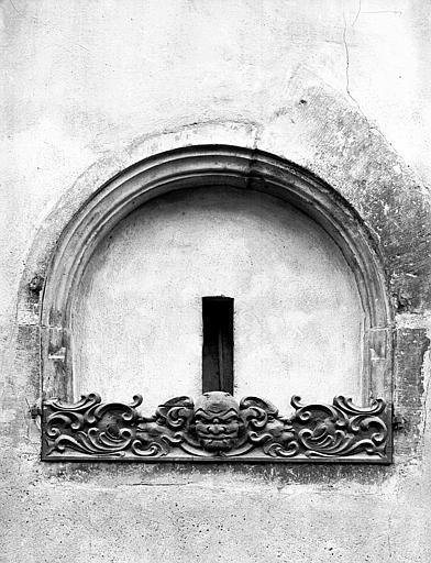 Fenêtre aveugle avec balustrade sculptée et masque grimaçant