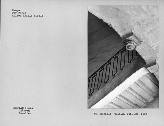 Partie supérieure de l'escalier vue par dessous, rampe en fer forgé