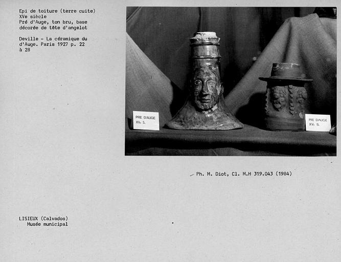 Epi de toiture en terre cuite vernissée, base décorée de tête d'angelot, ton brun, fabrication du Pré d'Auge