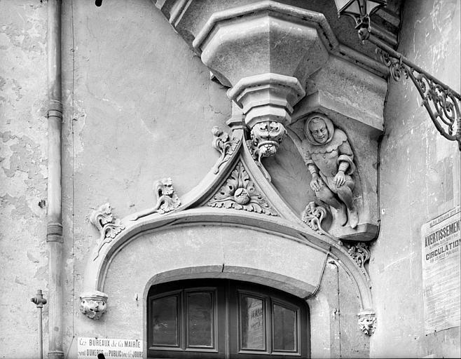 Entrée près du porche, côté intra-muros : fronton de porte, base de la tourelle à encorbellement et corbeau sculpté