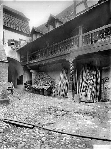 Cour intérieure : porche et galerie avec balustrade en bois