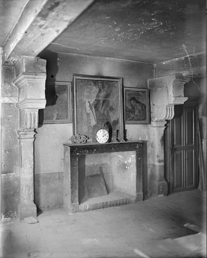 Intérieur d'une salle : cheminée, pendule, tableaux
