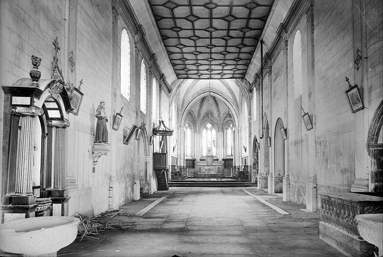 Vue de la nef vers le choeur : bénitiers, statue, peintures
