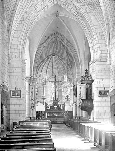 Vue intérieure de la nef vers le choeur. Groupe sculpté : Le Christ en croix entre la Vierge et saint Jean. Chaire à prêcher