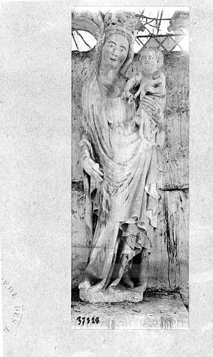 Statue en pierre polychrome : Vierge à l'Enfant. Vierge debout, couronnée, cambrée à droite, la main droite abaissée tenant un sceptre brisé. Sur son bras gauche, l'Enfant, le buste nu, tenant une colombe