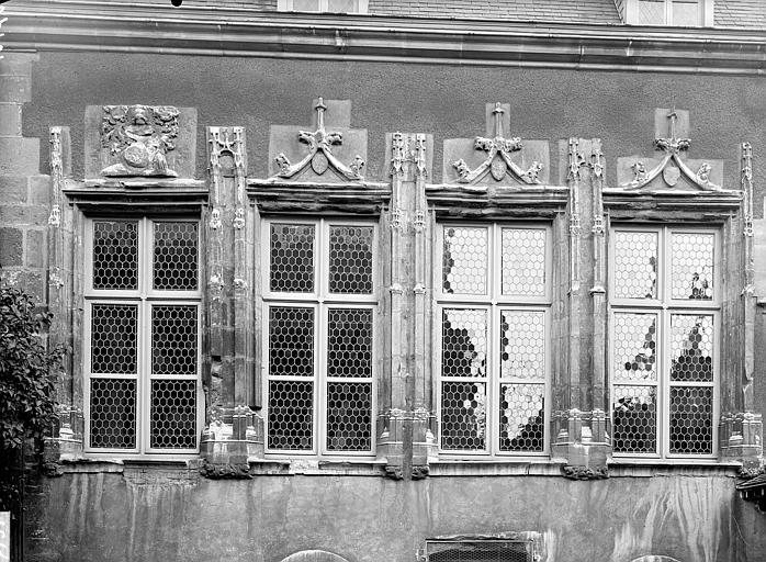 Pavillon sur cour, détail du premier étage : Fenêtres flamboyantes surmontées de bas-reliefs dont les armes de la famille