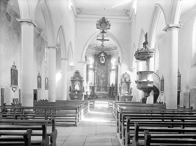 Vue intérieure de la nef vers le choeur. Calvaire au sommet de l'arc triomphal