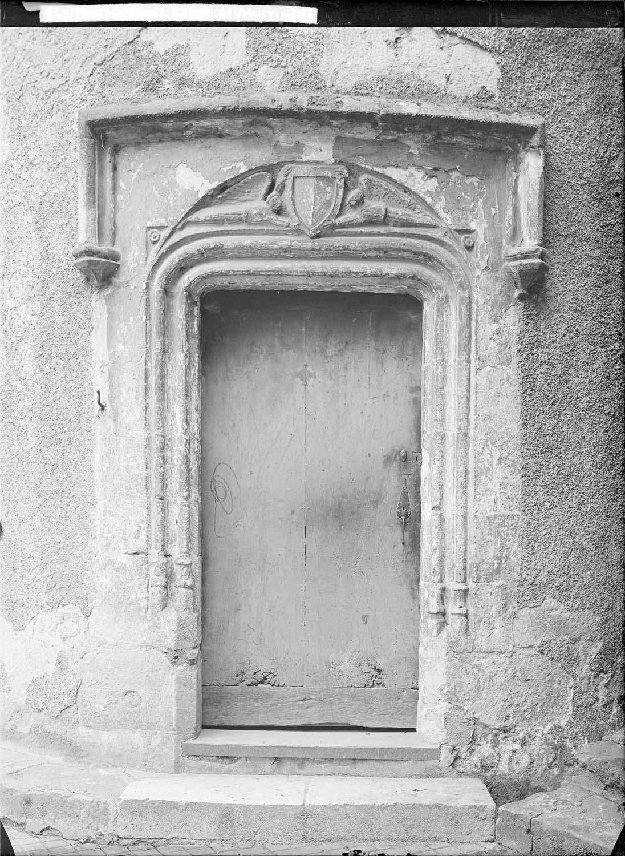 Portail Renaissance : ouverture en anse de panier moulurée surmontée dans un cartouche de deux anges étendus présentant un blason martelé