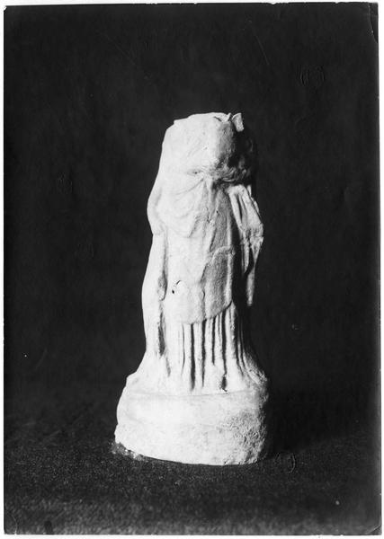 Statuette en terre cuite d'Aphrodite drapée, portant Eros sur le bras gauche. L'Aphrodite et l'Eros sont acéphales, Ier ou IIème siècle avant Jésus-Christ. Tombes de Topsin