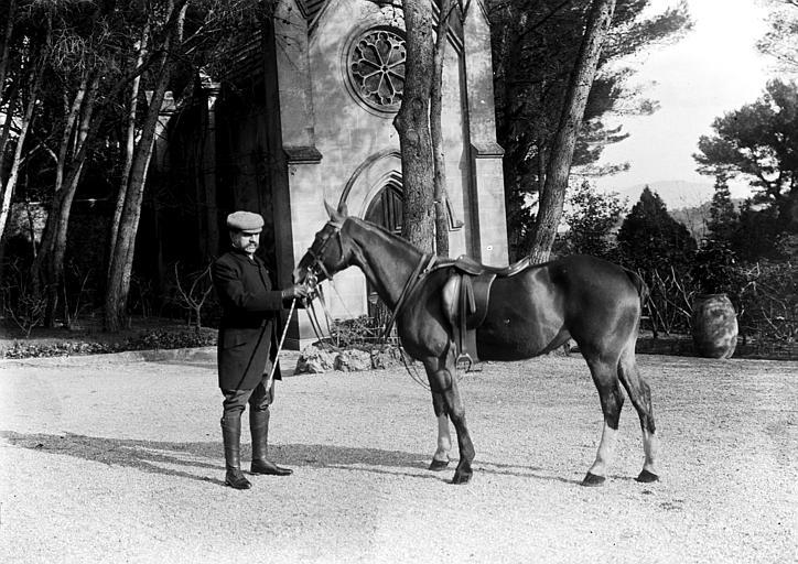 Présentation d'un cheval de selle près d'une chapelle : vue de profil avec le meneur