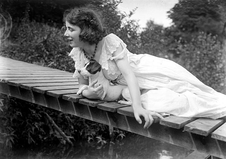 Mise en scène extérieure d'un modèle féminin : jeune femme allongée sur une passerelle avec son chien ratier dans les bras