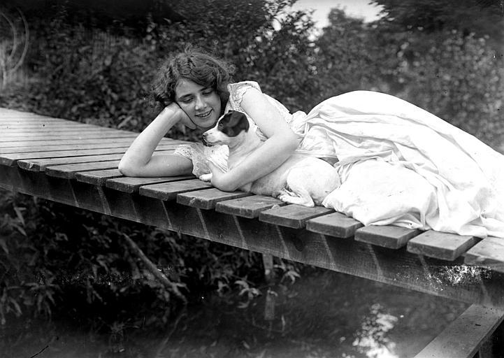 Mise en scène extérieure d'un modèle féminin : jeune femme allongée sur une passerelle regardant son chien ratier enserré dans ses bras