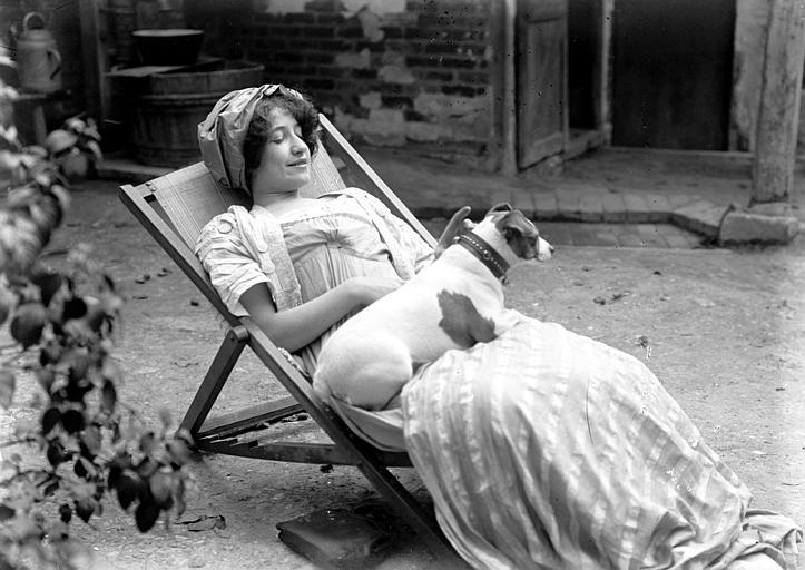 Mise en scène extérieure d'un modèle féminin : jeune femme portant un chapeau, allongée dans une chaise longue, avec son chien ratier sur ses jambes