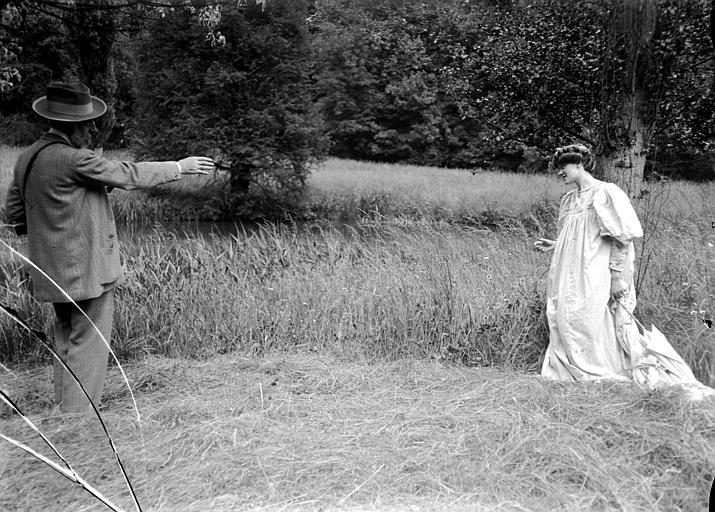 Scène en extérieur, campagne : un photographe, Robert Demachy (supposé), donne des directives de pose à une jeune femme costumée à la 'William Morris' (préraphaélisme)