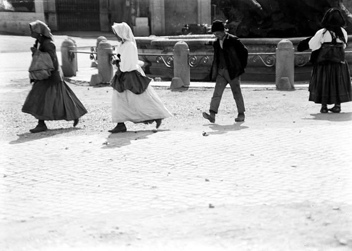 Scène de rue : homme et femmes se déplaçant sur une place, fontaine en arrière plan