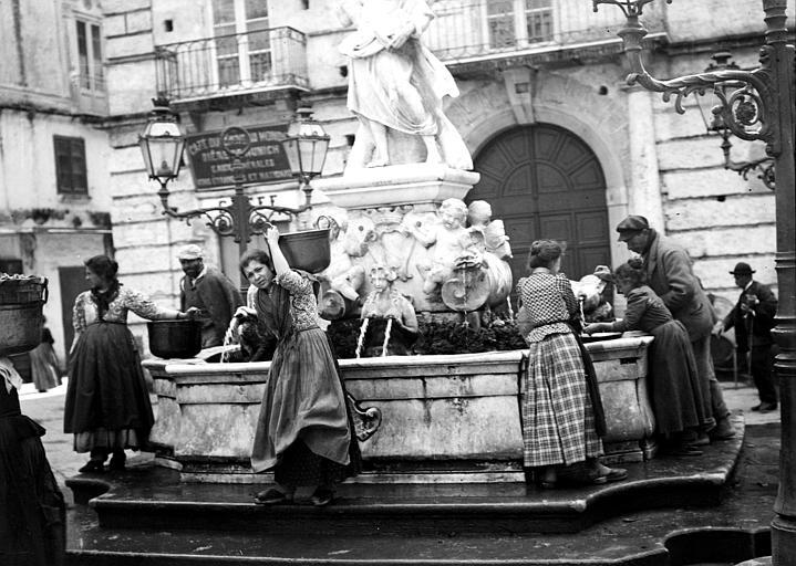 Scène de rue : hommes et femmes venant prendre de l'eau à une fontaine publique