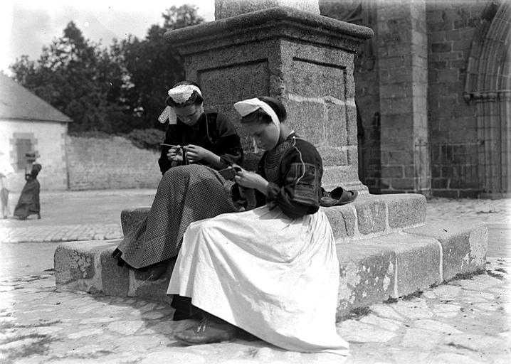 Bretonnes en costume traditionnel (type Pays Bigouden), assises au pied d'un calvaire, faisant du crochet