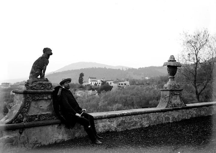 Promeneur assis sur un mur de jardin : vue sur une vallée et son village, sculpture de chien assis et vasque en pierre décorant le mur