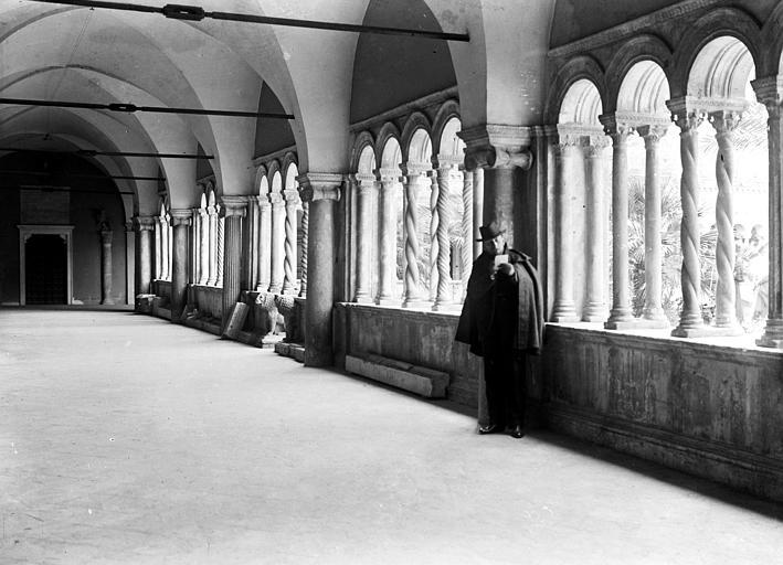 Homme adossé à une colonnette d'un cloître : galerie intérieure, deux lions en pierre sculptée encadrant l'une des entrées