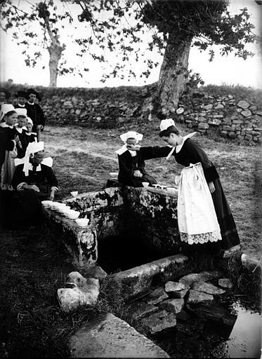 Groupe en costume traditionnel autour d'une fontaine-puits, scène de dévotion : bols disposés sur la margelle, pièce lancée dans l'eau