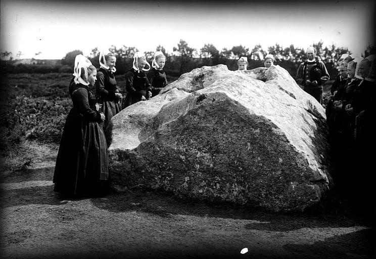 Groupe en costume traditionnel (type Pays Glazik) autour d'un mégalithe, chapelet à la main