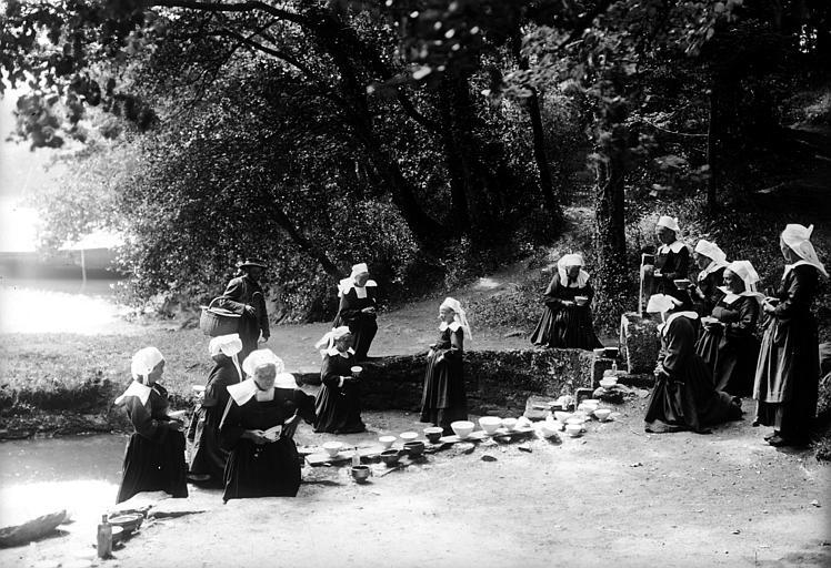 Groupe en costume traditionnel : femmes en prière près d'une fontaine, bols disposés sur une margelle